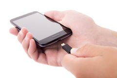 Smart phone with blank screen and charger in male hands isolated Stock Photos