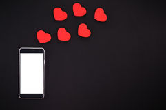 Smart phone with blank screen and hearts. On black background. Top view Royalty Free Stock Photos