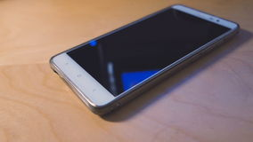 Smart phone with blank screen lying on wooden table stock video footage