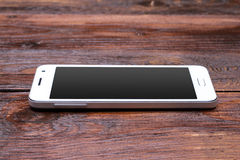 Smart phone with blank screen lying on wooden Stock Photos