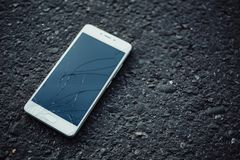 Smartphone with a broken screen. Smart phone with broken screen on dark background royalty free stock photo
