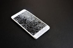 Smart phone with broken screen on dark background. White smart phone with broken screen on dark background stock image