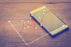 Smart phone and business graph analysis.jpg. Smartphone and business graph analysis business concept Royalty Free Stock Image