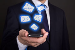 Smart phone in business man hand and flying envelopes Stock Photography