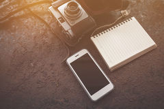 Smart phone with camera and notebook on ructic table Stock Photography