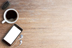 Smart phone,car key and earphone with cup of coffee on wood tabl Stock Image