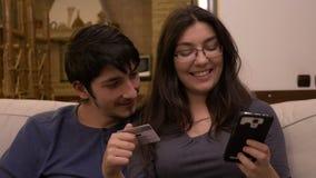 Smart Phone castana attraente della tenuta della donna ed introdurre i dati della carta di credito per comperare online stock footage