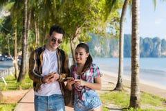 Smart Phone casuali delle cellule di uso delle coppie nel parco tropicale delle palme, bei giovani sorridenti felici che chiacchi Fotografia Stock Libera da Diritti