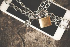 Smart phone with chain padlock on wooden table, mobile safety security concept. Background royalty free stock photography