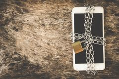 Smart phone with chain padlock on wooden table, mobile safety security concept. Background royalty free stock images