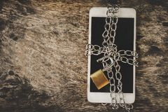Smart phone with chain and unlock padlock on wooden table, mobile unsafe security concept. Background royalty free stock photos