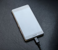 Smart phone charged by wire adapter close up stock photo Stock Photos