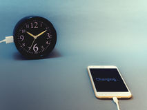 Smart phone charging time from clock Royalty Free Stock Photography
