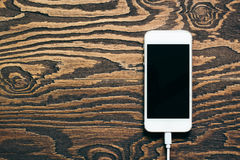 Smart phone charging on wooden desk Stock Images