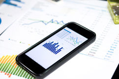Smart phone and chart. On the table Royalty Free Stock Photos