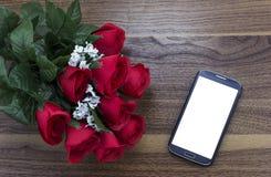 Smart Phone che pone accanto ad un mazzo delle rose Immagini Stock