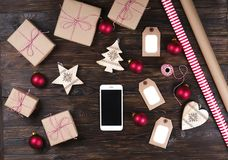 Smart phone with christmas presents on wooden background top view. Online holiday shopping concept. Flat lay, text space. Internet. Christmas background with Royalty Free Stock Photography