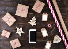 Smart phone with christmas presents on wooden background top view. Online holiday shopping concept. Flat lay, text space. Internet. Commerce on winter holidays Stock Images