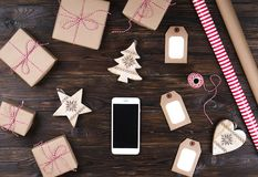 Smart phone with christmas presents on wooden background top view. Online holiday shopping concept. Flat lay, text space. Internet. Commerce on winter holidays Royalty Free Stock Photos