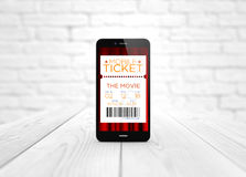 Smart phone cinema e-tickets over wooden table Stock Photo