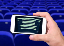 Smart phone and cinema ticket. Royalty Free Stock Images