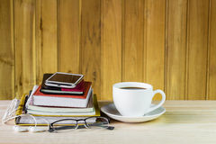 Smart phone,coffee cup,and stack of book on wooden table Royalty Free Stock Photography