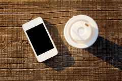 Smart phone and coffee cup on wooden surface Royalty Free Stock Photography