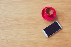 Smart phone with coffee cup on wooden table. View from above Royalty Free Stock Photo