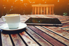 Smart phone and and coffee mug on a wooden table with empty chair Stock Photos