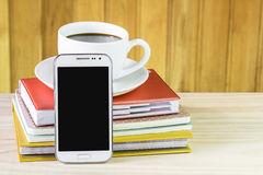 Smart phone, coffee and note book on wood table background. Royalty Free Stock Image