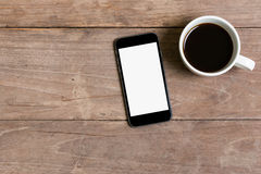 Smart phone and coffee. On Old wooden background royalty free stock images