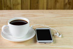 Smart phone and coffee on wooden table Stock Images