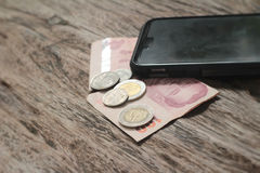 Smart phone with coins and banknotes on wood background Stock Images