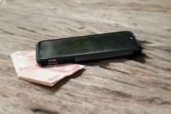 Smart phone with coins and banknotes on wood background Royalty Free Stock Photo