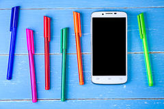 Smart phone and color pen on the blue wooden background Stock Photos
