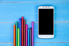 Smart phone and color pen on the blue wooden background Royalty Free Stock Photo