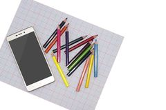Smart phone and colored pencils on a light background side view. mock up sample royalty free stock images