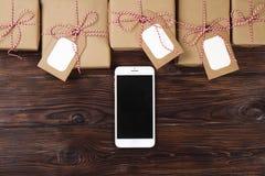 Smart Phone con i regali di Natale sulla vista superiore del fondo di legno Concetto online di shopping di festa Disposizione pia Fotografie Stock
