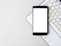 Smart Phone con il cellulare ed il computer portatile in bianco Lo Smart Phone con lo schermo in bianco e può essere aggiunge i v Fotografie Stock Libere da Diritti