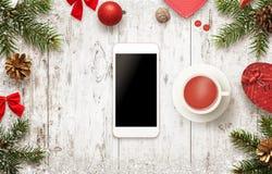 Smart Phone con le decorazioni di Natale sulla tavola Tè bevente e un irrompere i giorni di inverno Fotografie Stock