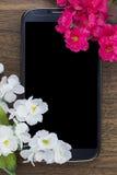 Smart Phone coperto da alcuni fiori rosa e bianchi Fotografie Stock