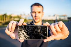 Smart phone with a cracked screen. Men`s hands hold a smart phone with a cracked screen stock image