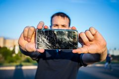 Smart phone with a cracked screen. Men`s hands hold a smart phone with a cracked screen stock photos