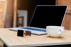 Smart phone and cup of coffee and laptop on woden desk.  Stock Image