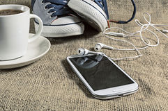 Smart phone  with cup of coffee and sneakers Royalty Free Stock Photography