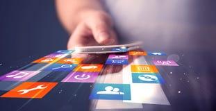 Smart Phone della tenuta dell'uomo con le icone dell'applicazione variopinte fotografia stock