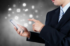 Smart Phone della tenuta dell'uomo d'affari che mostra icona, strategia aziendale Fotografia Stock
