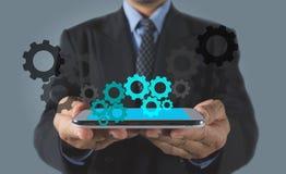 Smart Phone della tenuta dell'uomo d'affari con l'icona degli ingranaggi Fotografia Stock Libera da Diritti