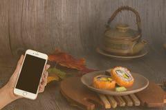 Smart Phone della tenuta della mano della donna sull'insieme giapponese vago dei sushi fotografia stock