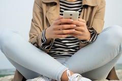 Smart Phone della tenuta della ragazza con due mani che si siedono sulla sabbia della spiaggia Immagine Stock Libera da Diritti